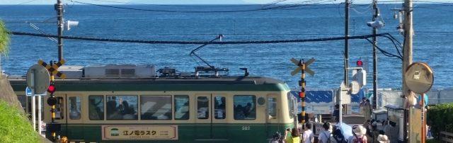 鎌倉高校前の駅の踏切で江ノ電が走っている