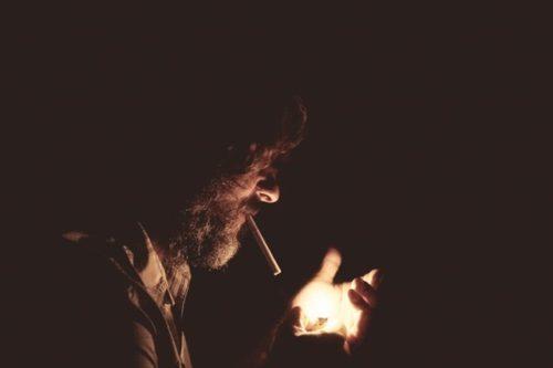 タバコに火をつけている男性