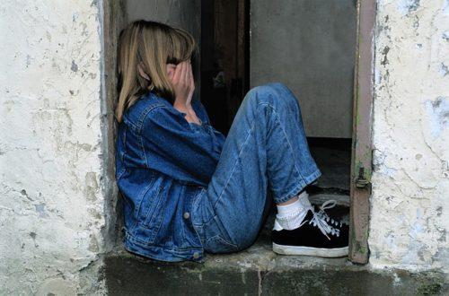 顔を隠しうずくまる外国人の女の子