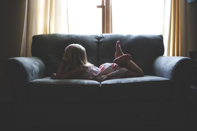 外国の少女がソファーで寝ている
